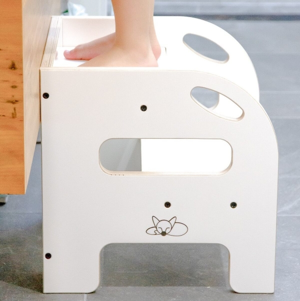 A child standing on the 2 up step in white