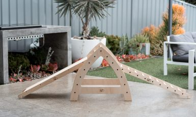 Slide, plank and marble run with ladder on the concrete outside.
