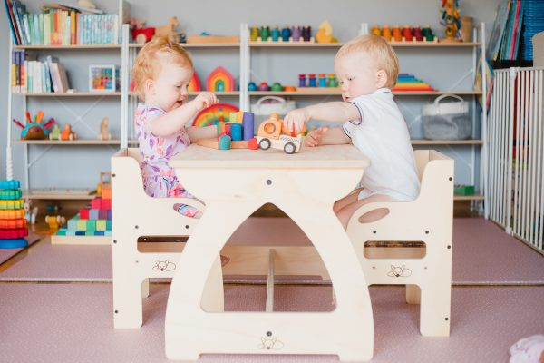 Two young children sitting at the timber table playing with wooden toys