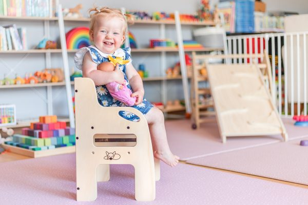 Little girl seated on wooden weaning chair and smiling