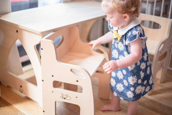 Little girl admiring the weaning chair in timber.