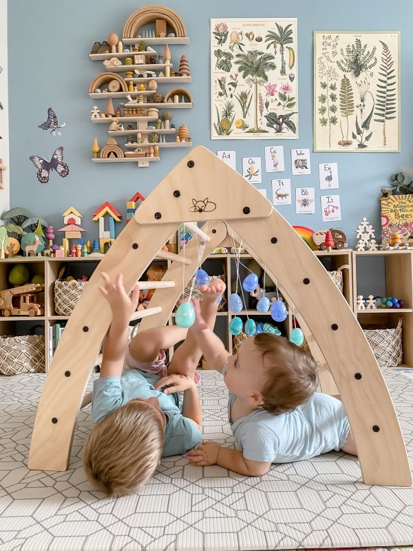 A baby and a toddle playing under the foldable pikler triangle