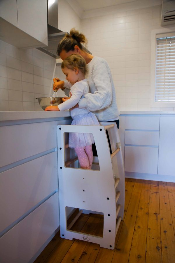 A little girl helping her mum using the learning tower