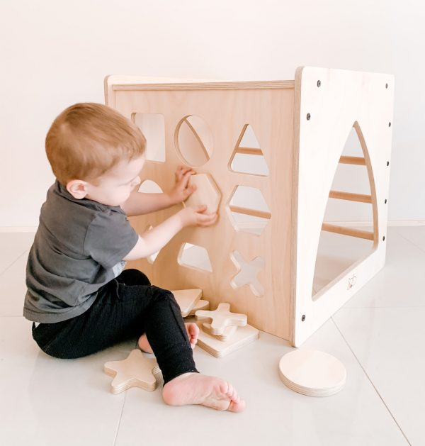 A child playing with a Montessori shape sorter cube