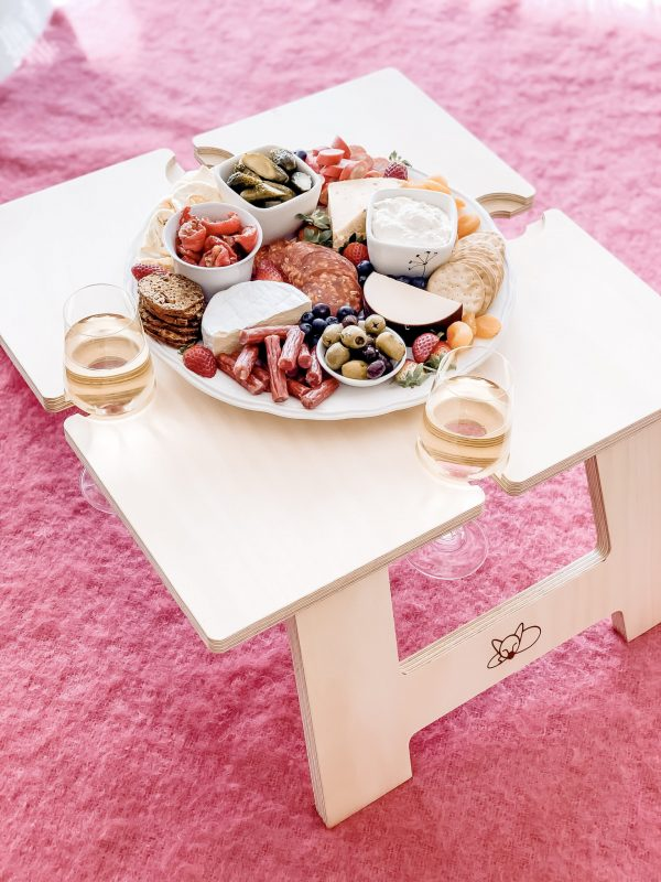 Square Wine Table on pink rug with food and wine