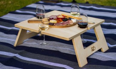 Square Wine Table on purple rug with food and wine