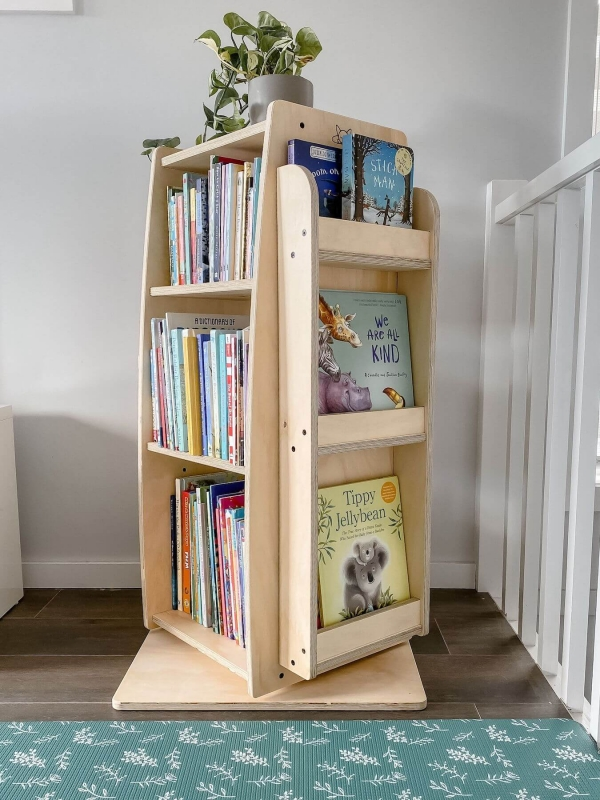 The bookworm rotating bookshelf filled with children's books and a green plant on top.