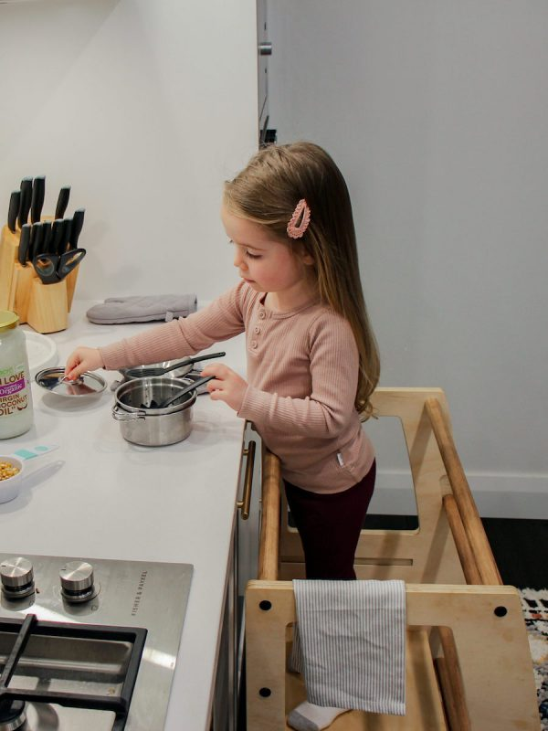 A little girl cooking while standing on the My Little Helper Double -Timber Finish