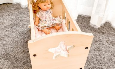 A doll cradle with a dolly inside