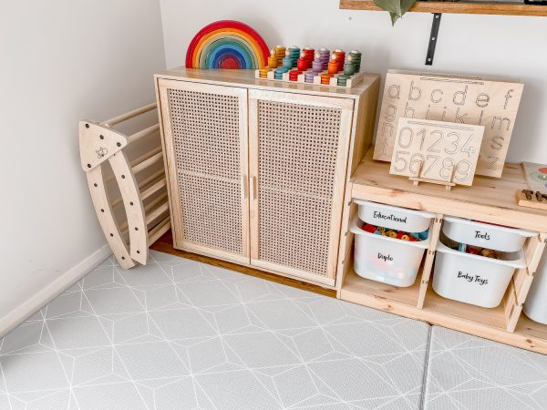 Foldable arch stored neatly beside a toy storage cupboard in a montessori playroom. Also pictured are letter and number tracing boards