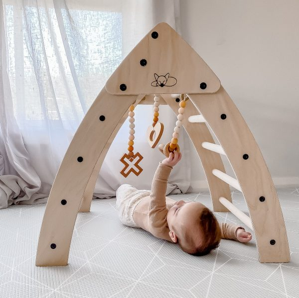 A baby lying underneath the foldable pikler