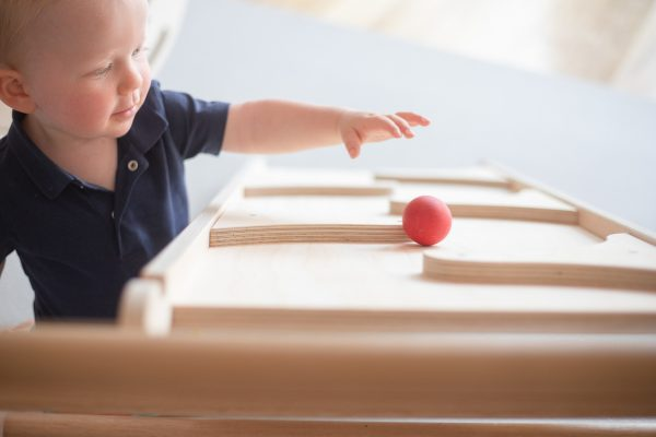 A toddler rolling a red ball down the marble run.