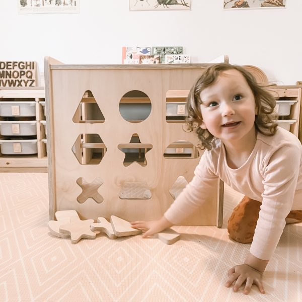 A shape sorter cube and a happy child.