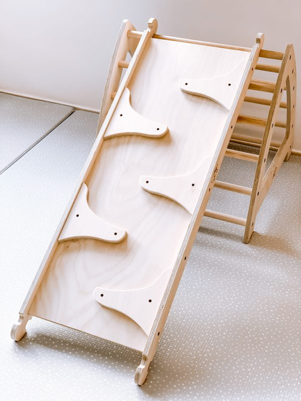 Wooden marble run attached to wooden pikler triangle