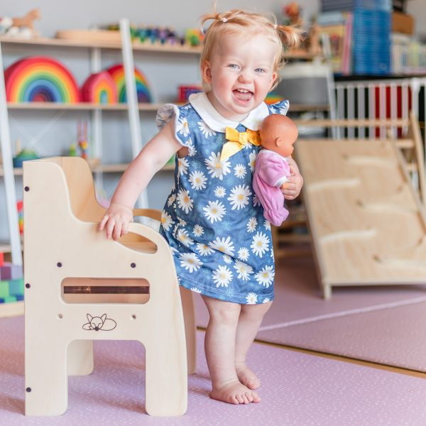A little girl standing up from a weaning chair